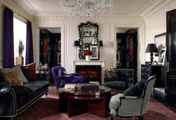 חדר אירוח: ספת עור שחורה, שלוש כורסאות, שידה, מנורת תקרה, שלוש מנורות שולחן, שטיח