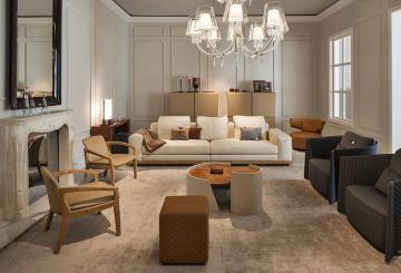 חדר אירוח בריטי עם ספה, שלושה כורסאות, שתי כסאות, פופ, שולחן קפה, שתי שידות, שטיח, מנורת תקרה, מנורה ועומדת קטנה