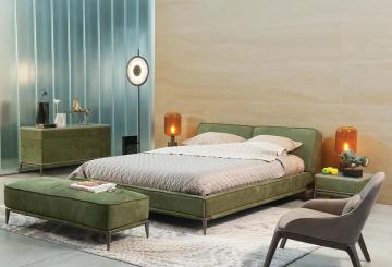 חדר שינה יוקרתי, מיטה זוגית מעוצבת, שידת צד, שתי מנורות שולחן, מנורת רקצפה עומדת, שידה גדולה, כיסא מרופד, פופ ושטיח יוקרתי